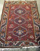 A Small Persian Rug, Decorated with geometric medallions and motifs on a red ground, 118 x 87cm