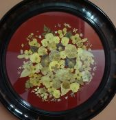 A Collage of Pressed Flowers, on a red velour backing, 44cm diameter, in an ebonised circular frame