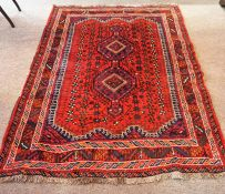 An Iranian Shiraz Rug, Decorated with two central geometric medallions on a red ground, 197 x 145cm