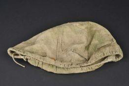Couvre casque de fabrication terrain En forte toile grise, ajout de tâches vertes et ocres à la