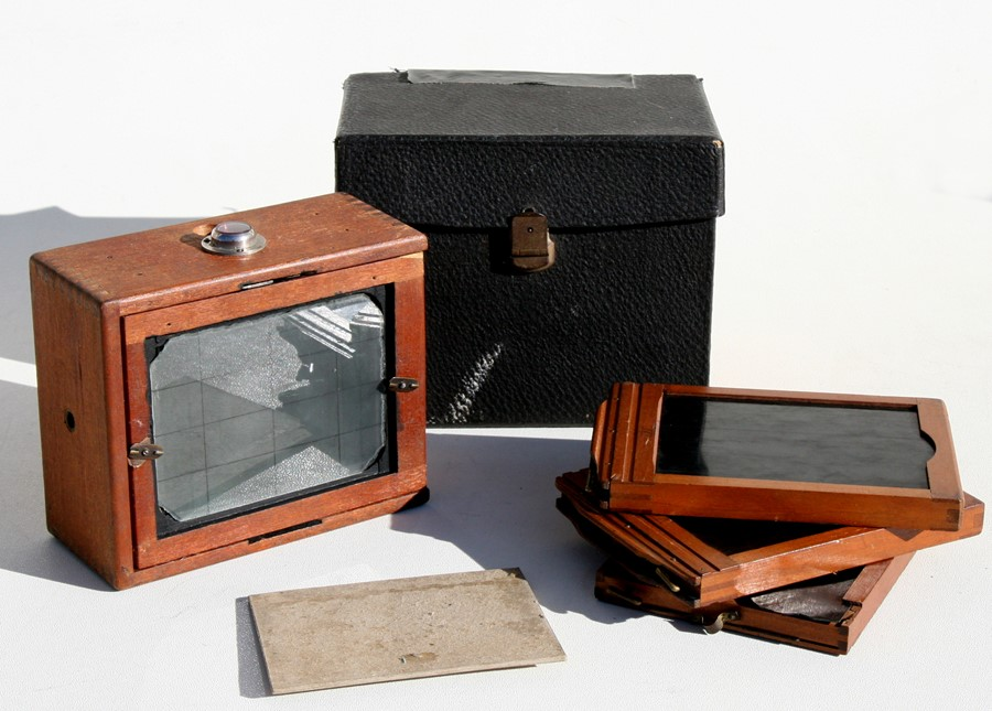 Lot 54 - A cased Bellows camera with additional plates.