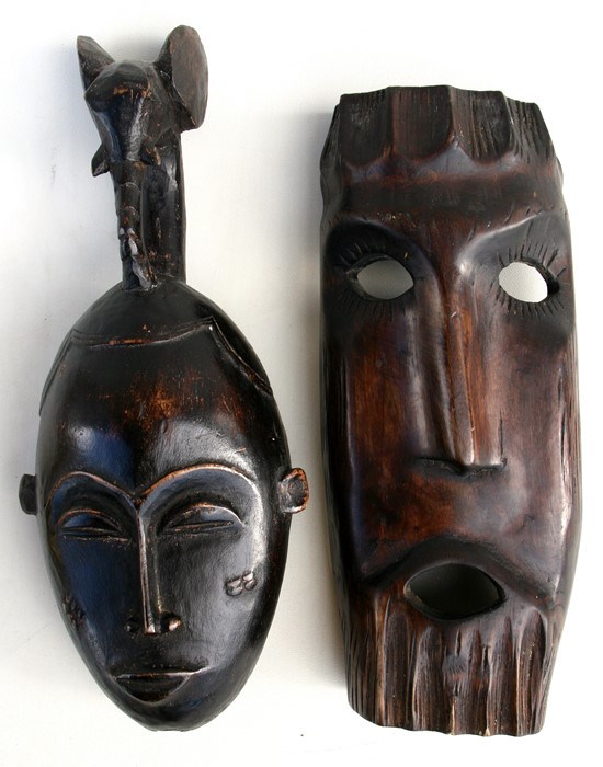 Lot 41 - An African carved hardwood mask; together with another similar.