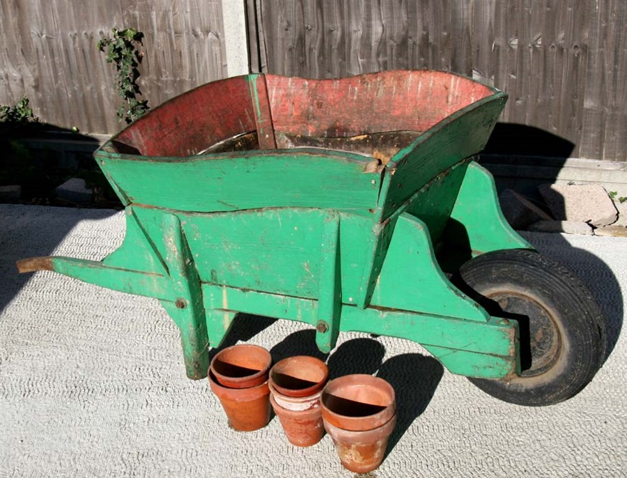 Lot 8 - A late 19th / early 20th century green painted wooden wheelbarrow, 163cms (64ins) long; together