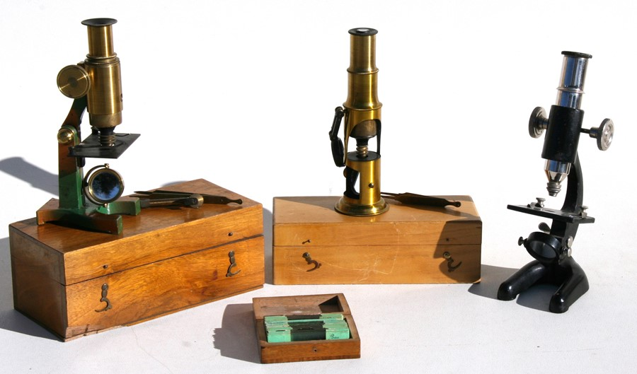 Lot 55 - Two lacquered brass student microscopes, boxed; another microscope, together with a box of