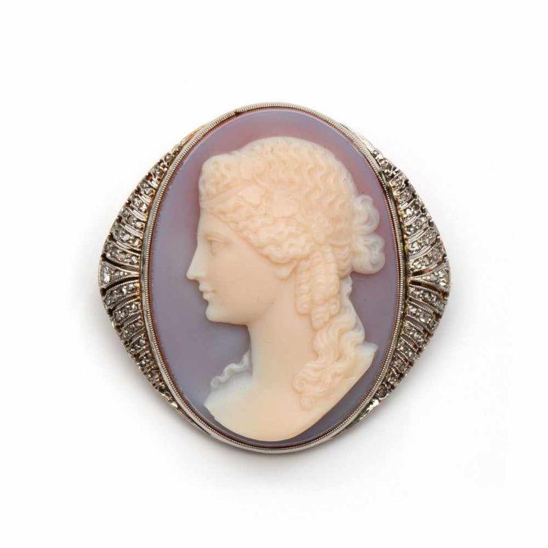 Lot 55 - Zilveren en gouden cameebroche, ca. 1910,Camee met voorstelling van een dame met krullend haar en