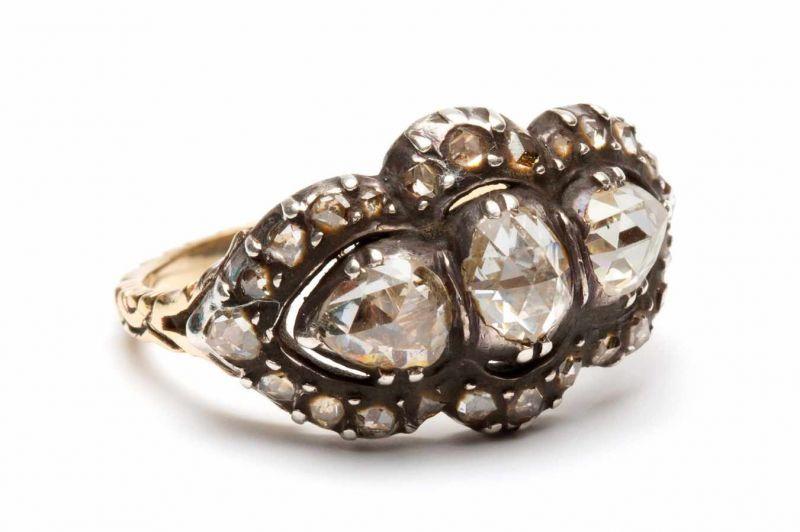 Lot 38 - Zilveren en gouden rijringgezet met één ovale en twee peervormige roosdiamanten in geschulpte