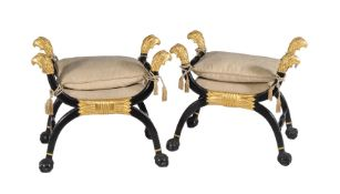 A pair of ebonised and parcel gilt x-frame stools in Regency style