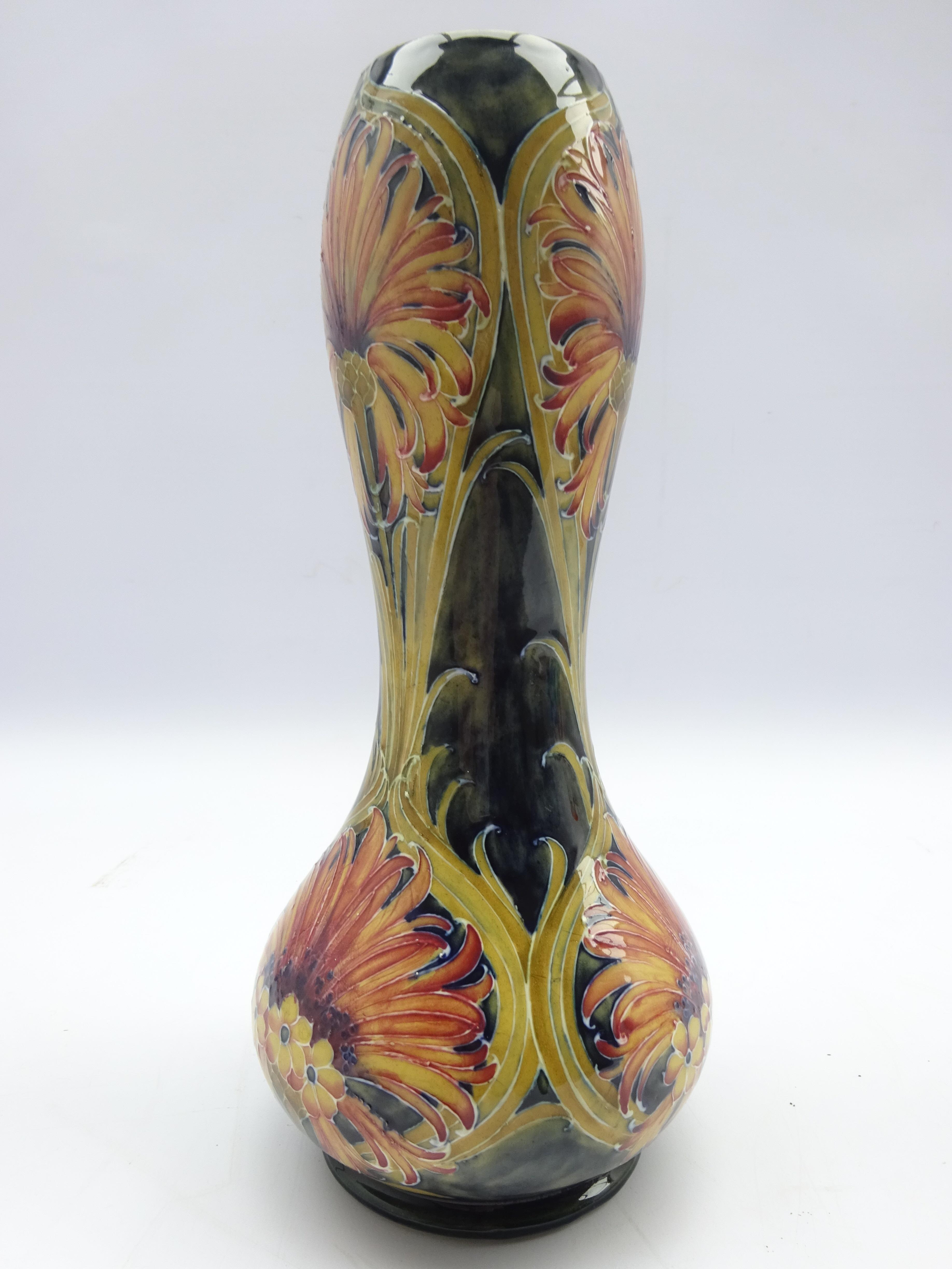 Lot 3 - William Moorcroft vase decorated with the revived cornflower pattern in peach and on a green ground