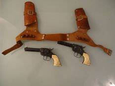 A PAIR OF METAL CAP PISTOLS - by Daisy in leather