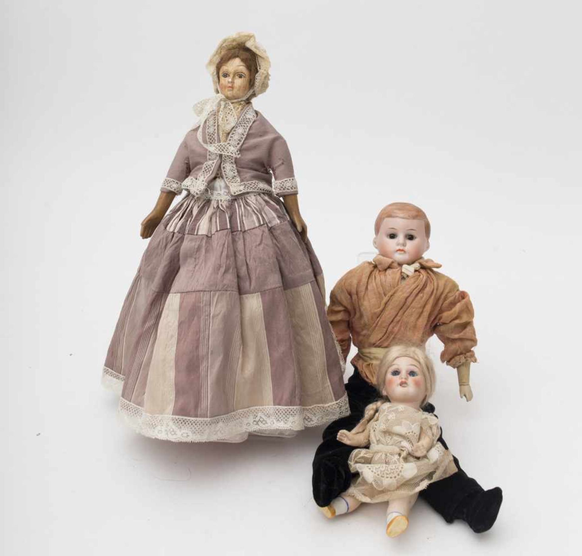 Three dolls One a full-headed boy, fabric body, H=32cm – another one fashionable with wooden head