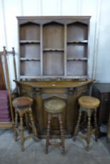 Lot 29 - A carved oak bar and three stools