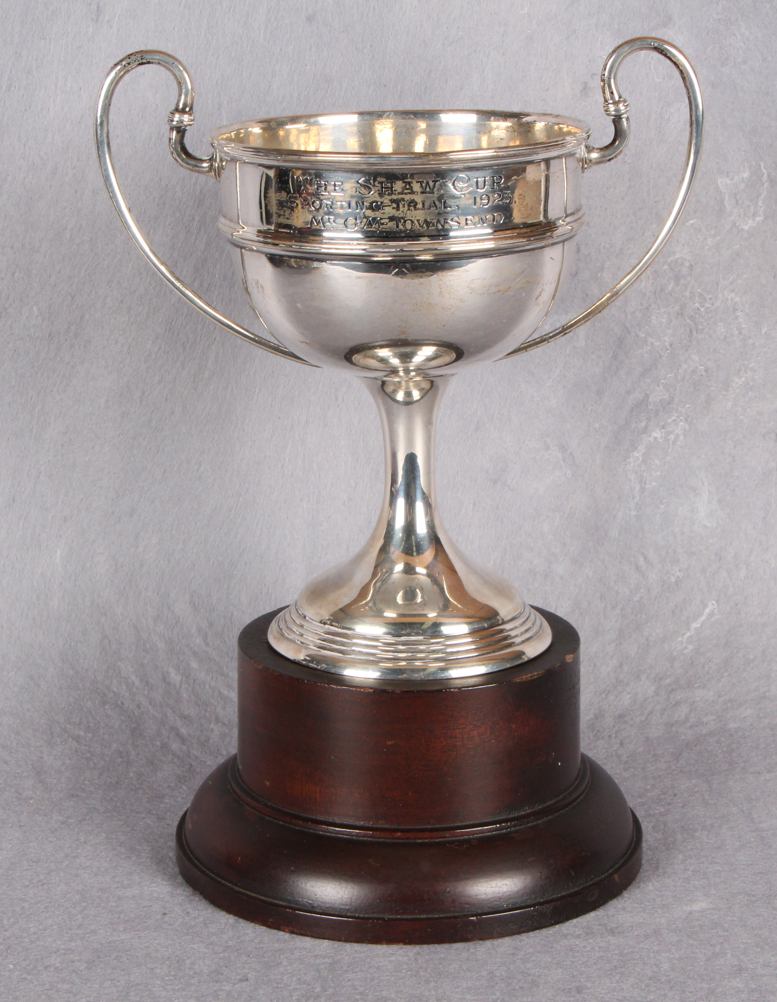 "Lot 34 - A two-handled circular section sports trophy ""The Shaw Cup"" spreading circular base,"