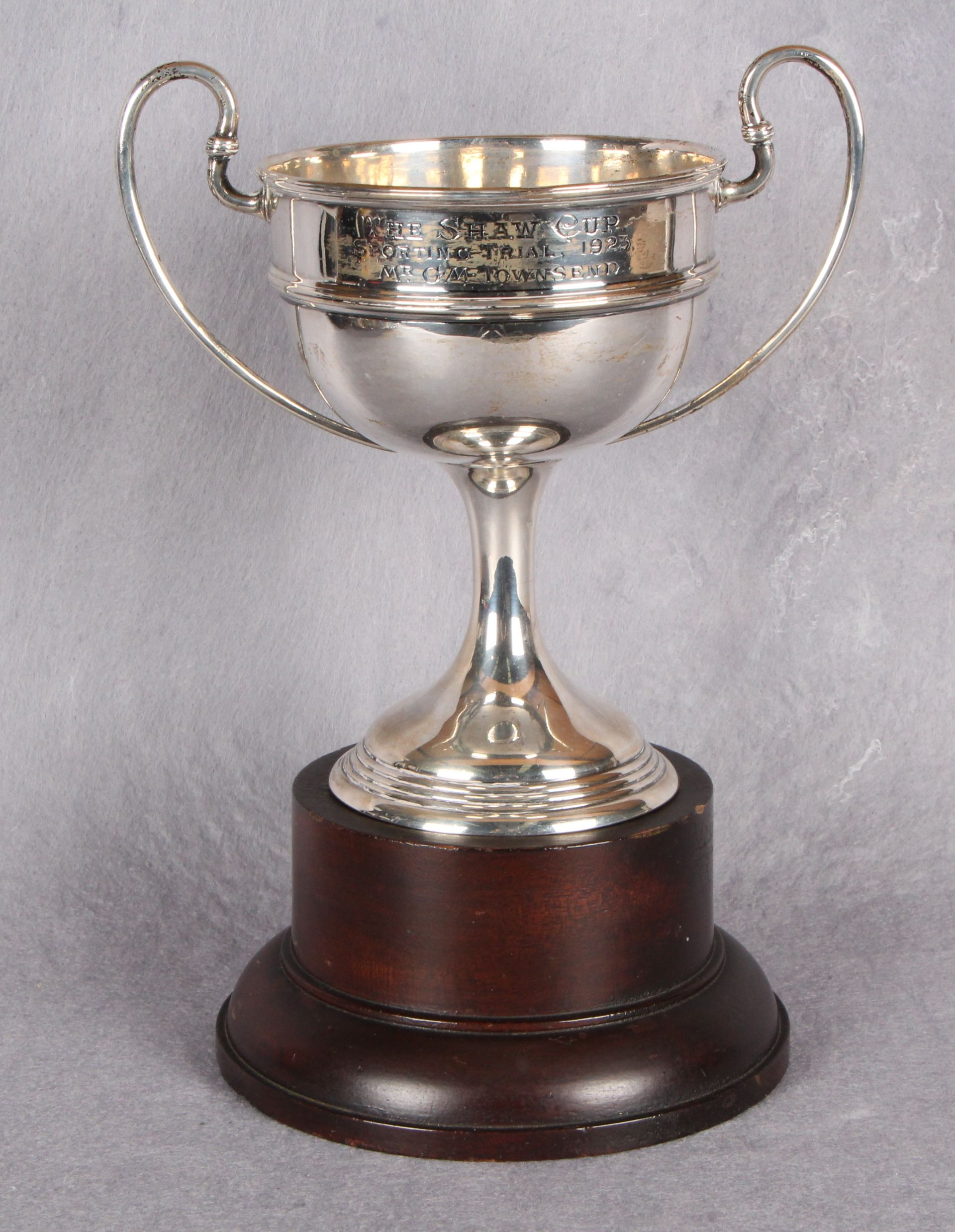 """Lot 34 - A two-handled circular section sports trophy """"The Shaw Cup"""" spreading circular base,"""
