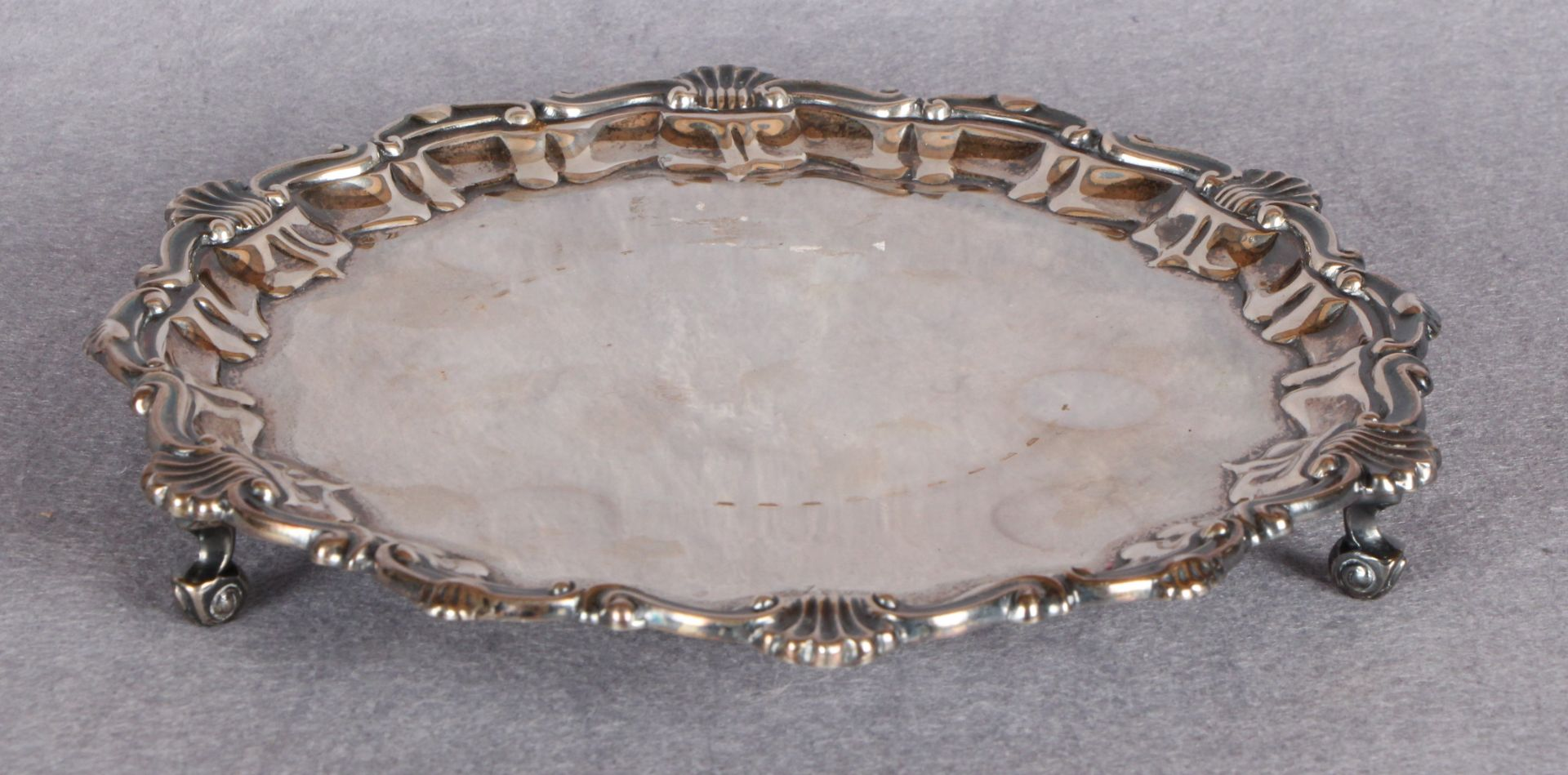 Lot 35 - A Georgian style silver shaped circular card tray, with shell moulded border, three scroll feet,