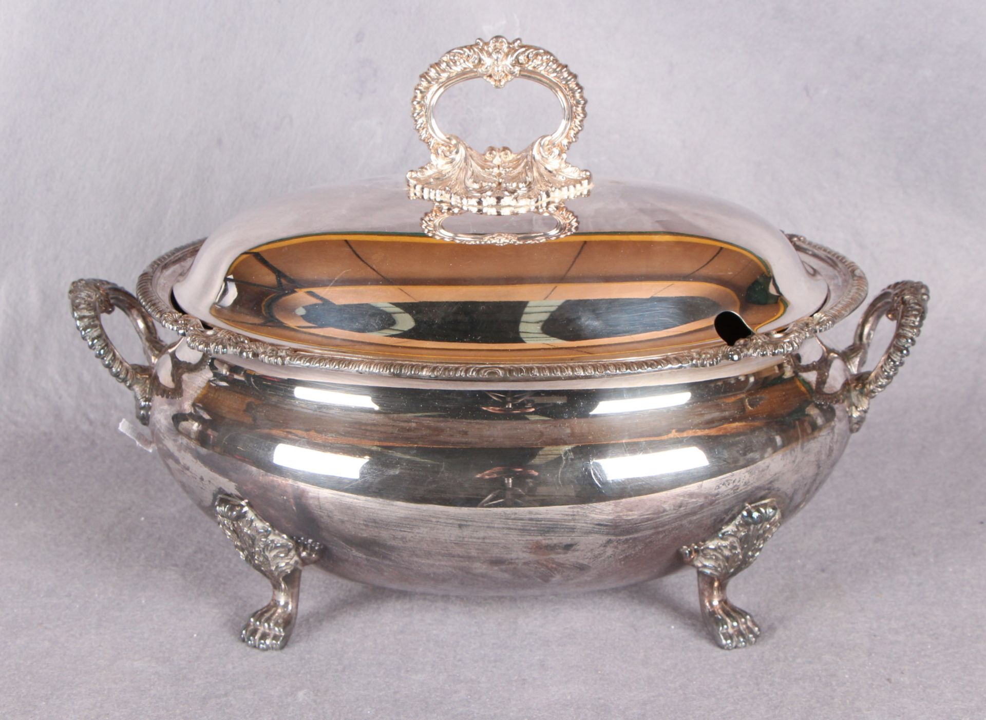 """Lot 3 - An oval soup tureen and cover, with cast borders, handles and lion paw supports, stamped """"Harrods,"""