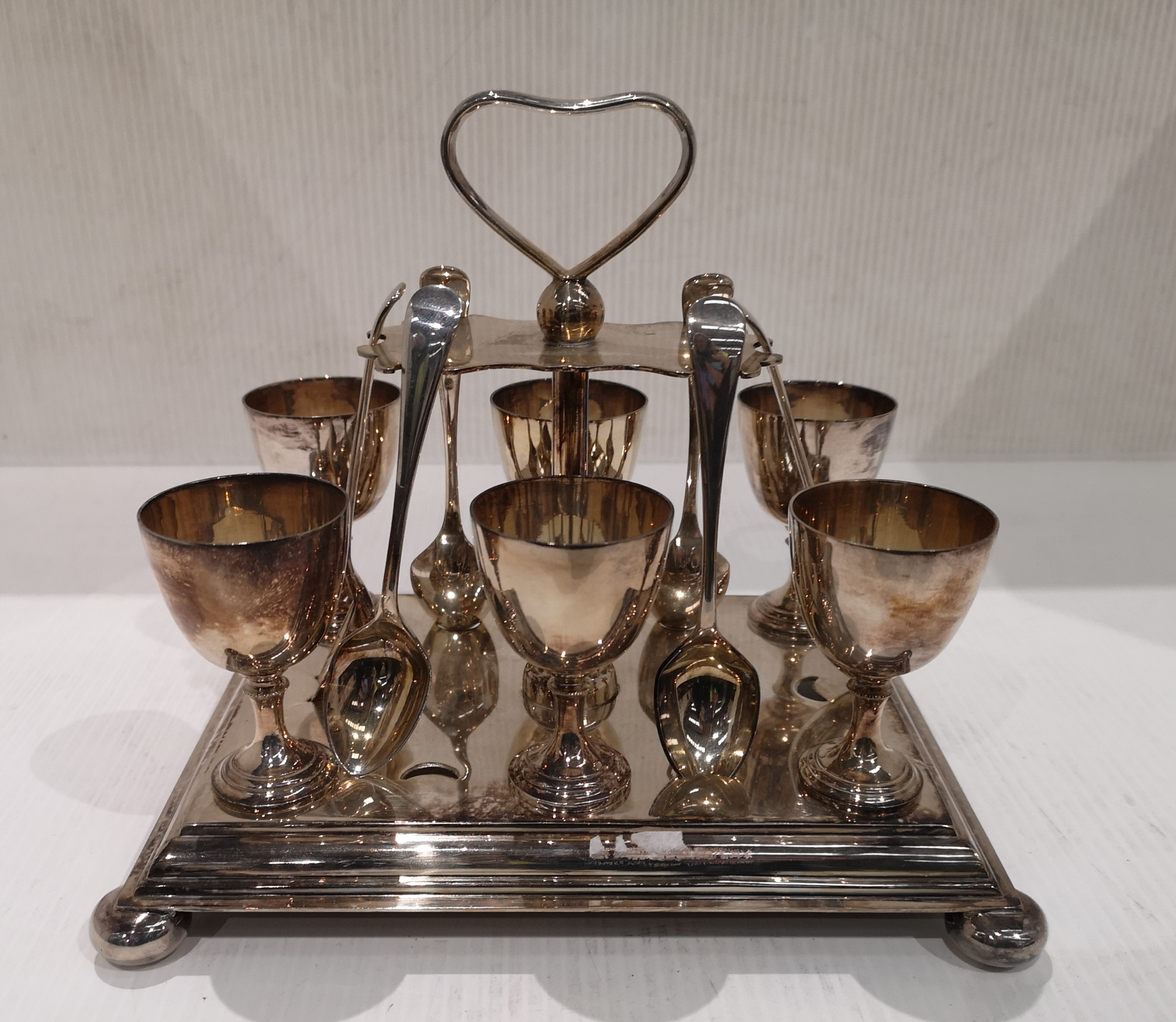 Lot 24 - A plated six piece egg cup and spoon stand