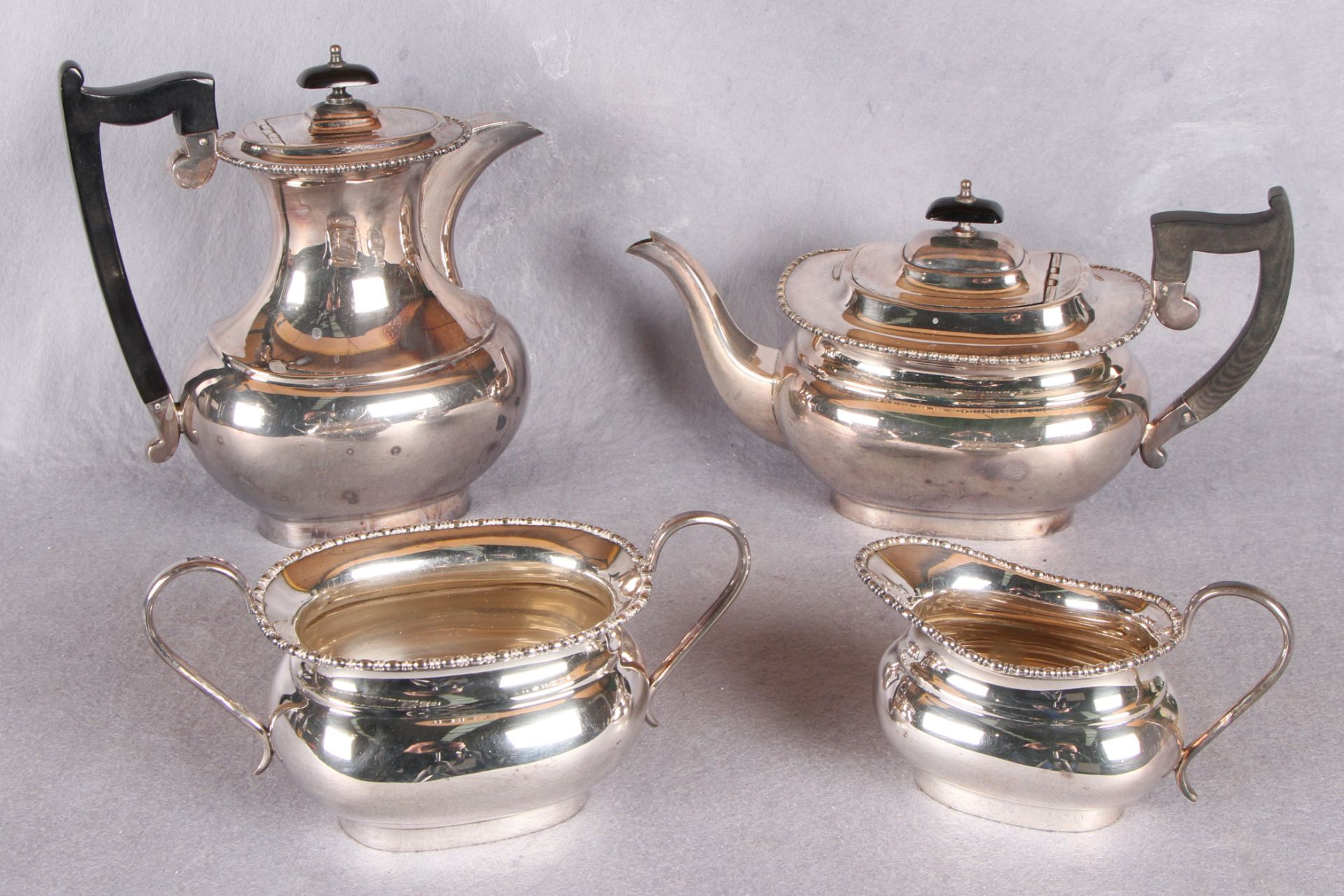 Lot 4 - A four piece tea service, of rounded rectangular form, beaded borders,