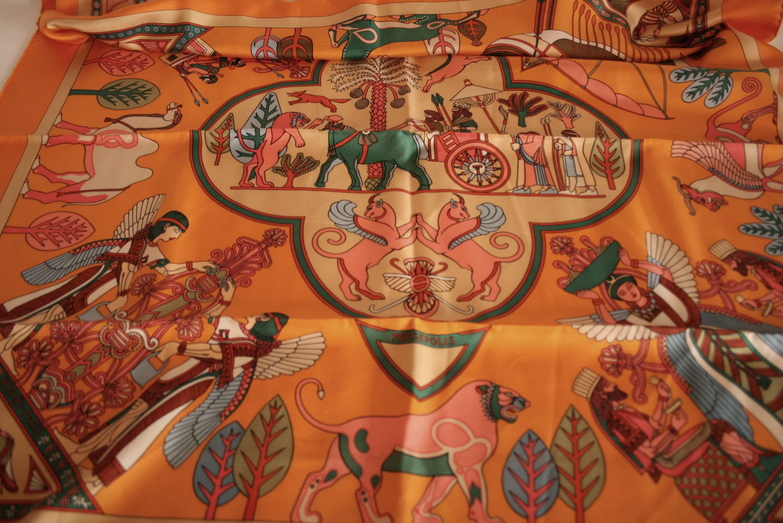 """Lot 31 - Carré en soie HERMES aux motifs orange """"PERSEPOLIS"""" - HERMES silk scarf with orange [...]"""