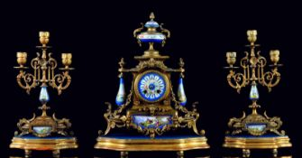 A GILT SPELTER AND SEVRES STYLE APPLIQUÉS CHIMNEY GARNITURE CONSISTING OF CLOCK, TWO CANDELABRAS AND