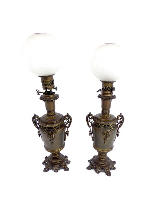 Lot 33 - A pair of bronze lamp bases with spherical frosted glass shades