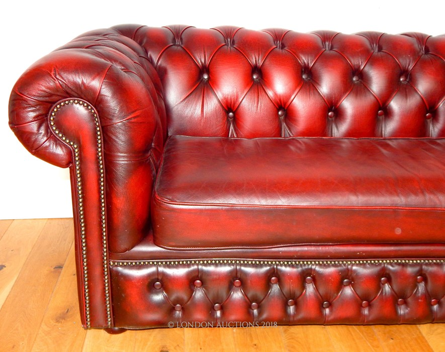 Lot 32 - A red leather Chesterfield sofa