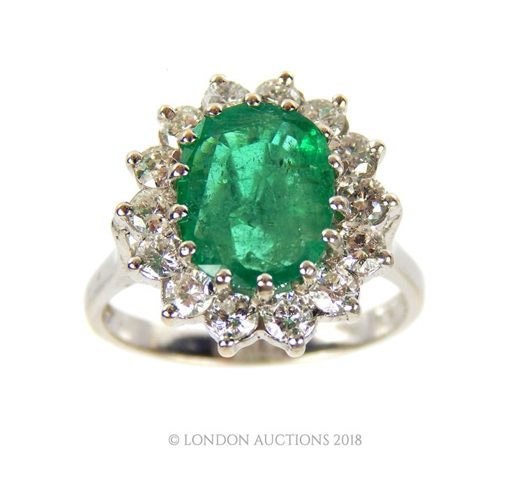 Lot 8 - A good 18 Carat White Gold Emerald and Diamond Cluster Ring.
