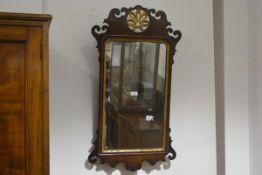 A George III style parcel gilt walnut fretwork mirror, with stylised pierced foliate crest over a