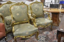 A pair of large Napoleon III style giltwood fauteuils, each with cartouche back above a stuffed-over