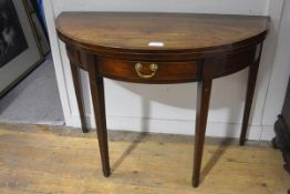 A George III mahogany demilune foldover tea table, the crossbanded top over a frieze drawer and