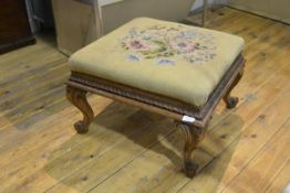 A Louis XV style walnut low stool, the square needlework seat raised on cabriole legs carved with