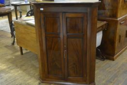 A George III mahogany hanging corner cupboard, early 19th century, the moulded cornice above a