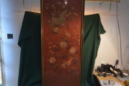 An Oriental silk needlework panel, worked with pheasants amidst flowering boughs against a deep