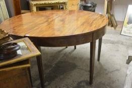 A George III mahogany D-end dining table, each demilune half with plain frieze and raised on