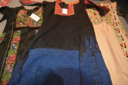 Three Palestinian kaftans; the first in black with blue needlework panels below and embroidered silk