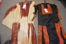 Two Palestinian kaftans; the first in cream linen with needlework panels and embroidered