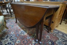 A George III mahogany gateleg dining table, the substantial oval top with twin leaves raised on