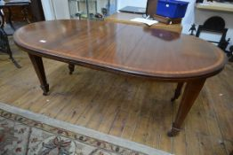 An Edwardian inlaid mahogany wind-out dining table in 18th century style, with two leaves, raised on