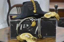 A Royal Navy officer's cased bicorn hat, epaulettes and sword belt, early 20th century, Gieves