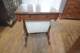 A mid-Victorian walnut work table, the moulded rectangular top over a frieze drawer fitted for