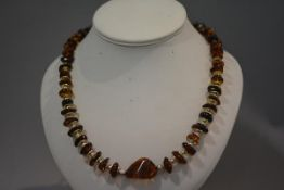 A Continental silver and amber (untested) necklace, composed of graduated, shaped bouton beads
