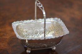 An Edwardian silver swing-handled sugar basket, of cauldron form, with scroll cast rim, raised on