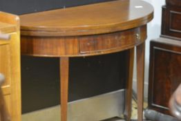 A George III mahogany demilune foldover tea table, with single frieze drawer and rasied on