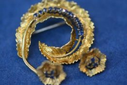 An 18ct gold and sapphire brooch with a pair of earrings en suite, the brooch modelled as a curled