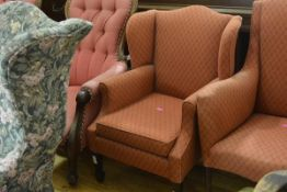A small Edwardian lady's wing chair, raised on square section tapering legs terminating in spade