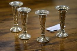 A set of four Edwardian silver bud vases, Martin Hall & Co., Birmingham 1903, weighted. 10.5cm