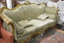 A large Napoleon III style giltwood canape, with scroll and leaf-carved crest and outswept arms