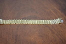 An 18ct gold bracelet of shaped plaited links, hallmarke en suite with the preceding lot Length