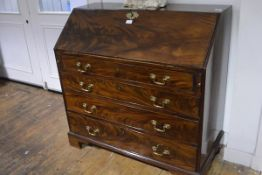 A George III mahogany bureau, c. 1800, the slant front enclosing a fitted interior over four