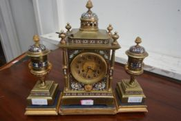 A late 19th century French champleve enamel and brass clock garniture, the dial with Arabic numerals