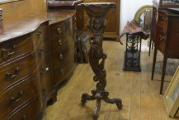 A Continental walnut torchere, early 18th century, the top carved as a conch shell and with